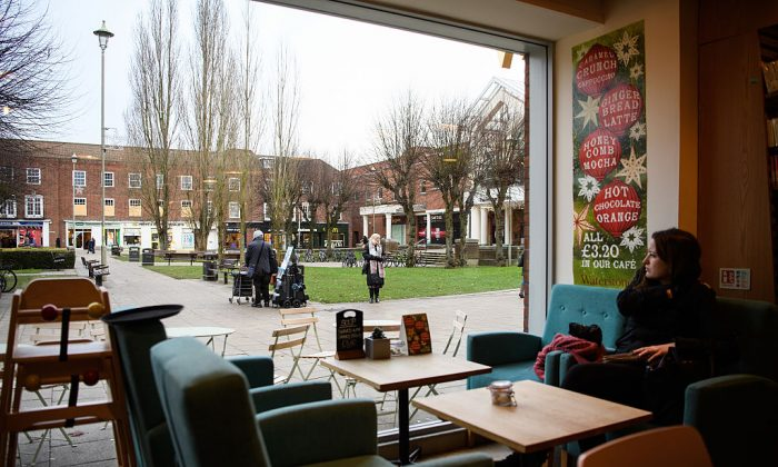 A woman looks from a coffee shop window to the town centre in Welwyn Garden City, England on Jan. 4, 2017. (Leon Neal/Getty Images)