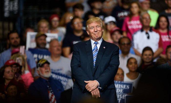 President Donald J. Trump listens as West Virginia Governor Jim Justice announces that he is switching parties to become a republican during the president's campaign rally at the Big Sandy Superstore Arena on August 3, 2017 in Huntington, West Virginia. (Photo by Justin Merriman/Getty Images)