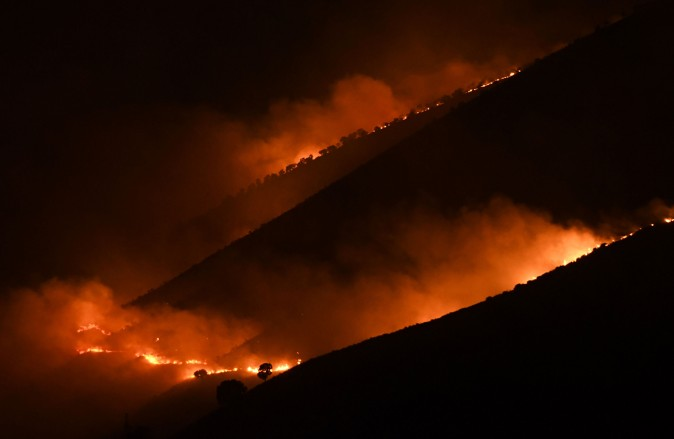Flames and smoke rise from a forest in fire near Sarande in the Muzina mountain region, southern Albania, on Aug. 9, 2017. (GENT SHKULLAKU/AFP/Getty Images)