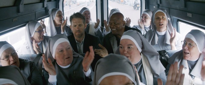 (L–R) Darius Kincaid (Samuel L Jackson), and Michael Bryce (Ryan Reynolds) among a plethora of nuns in