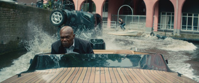 Darius Kincaid (Samuel L. Jackson) piloting a speedboat down a dutch canal, in