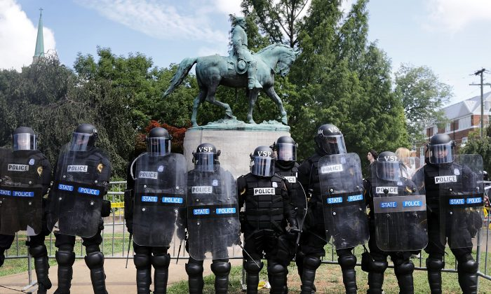 "Virginia State Police in riot gear stand in front of the statue of General Robert E. Lee before forcing white nationalists, neo-Nazis and members of the ""alt-right"" out of Emancipation Park after the ""Unite the Right"" rally was declared an unlawful gathering Aug. 12, 2017 in Charlottesville, Virginia. (Chip Somodevilla/Getty Images)"
