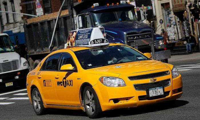 A taxi cab drives on a street  in New York City.  (Photo by Chris Hondros/Getty Images)
