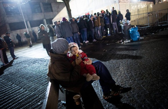 A man from Syria feeds his daughter as asylum seekers line up in front of the State Office of Health and Social Affairs (LAGeSo) registration centre in Berlin on December 21, 2015. (KAY NIETFELD/AFP/Getty Images)