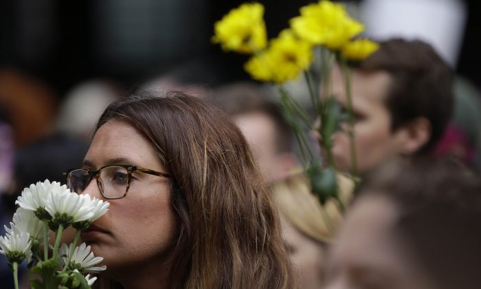 People hold flowers at a vigil in Chicago on Aug. 13 a day after a call drove into a crowd at a protest in Charlottesville killing 32-year-old Heather Heyer. (JOSHUA LOTT/AFP/Getty Images)