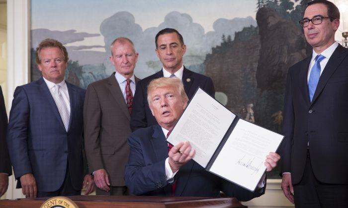 President Donald J. Trump signs a memorandum on addressing China's laws, policies, practices, and actions related to intellectual property, innovation, and technology at The White House in Washington on Aug. 14, 2017.  (Chris Kleponis-Pool/Getty Images)