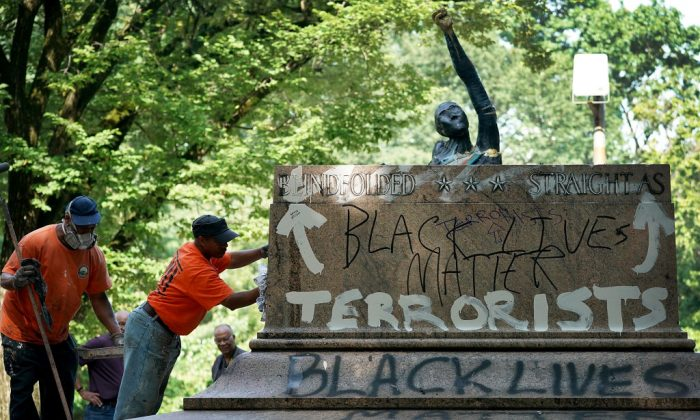 "Baltimore city workers remove graffiti from the pedestal where a statue dedicated to Robert E. Lee and Thomas ""Stonewall"" Jackson stood August 16, 2017 in Baltimore, Maryland. (Win McNamee/Getty Images)"
