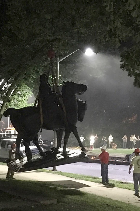 "Workers load statues of Confederate generals Robert E. Lee and Thomas ""Stonewall"" Jackson on a flatbed truck in the early hours of August 16, 2017 in Baltimore, Maryland. (ALEC MACGILLIS/AFP/Getty Images)"