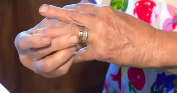 Mary Grams slips her engagement ring on her finger after missing it for 13 years. Her daughter-in-law found it growing on a carrot. (Screenshot via Reuters)