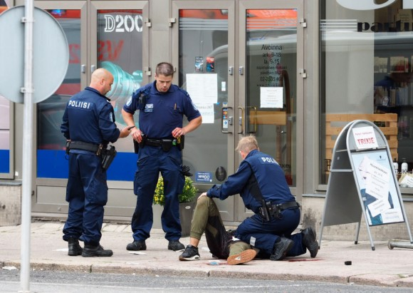 Police officers stand next to a person lying on the pavement in the Finnish city of Turku where several people were stabbed on August 18, 2017. (KIRSI KANERVA/AFP/Getty Images)