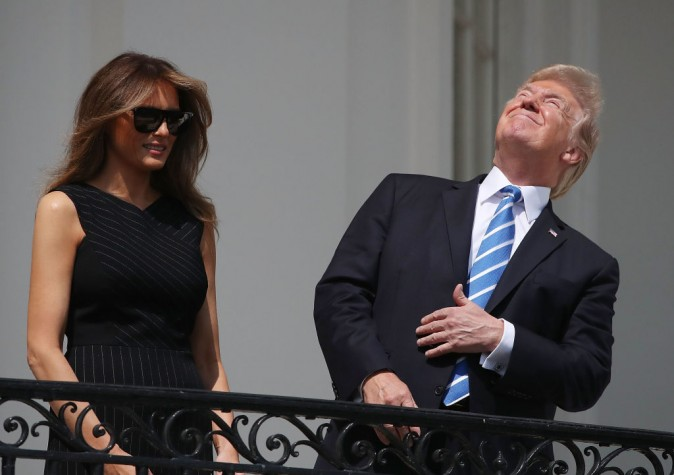 "WASHINGTON, DC - AUGUST 21:  (AFP OUT) U.S. President Donald Trump looks up toward the Solar Eclipse while joined by his wife first lady Melania Trump on the Truman Balcony at the White House on August 21, 2017 in Washington, DC. Millions of people have flocked to areas of the U.S. that are in the ""path of totality"" in order to experience a total solar eclipse.  (Photo by Mark Wilson/Getty Images)"