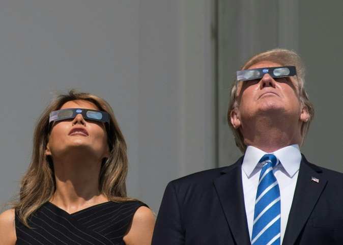 US President Donald Trump and First Lady Melania Trump look up at the partial solar eclipse from the balcony of the White House in Washington, DC, on August 21, 2017. The Great American Eclipse completed its journey across the United States Monday, with the path of totality stretching coast-to-coast for the first time in nearly a century. / AFP PHOTO / NICHOLAS KAMM        (Photo credit should read NICHOLAS KAMM/AFP/Getty Images)