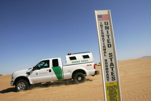 A Border Patrol vehicle passes an international border marker in the Colorado Desert at the Imperial Sand Dunes along the US–Mexico border between El Centro, Calif., and Yuma, Ariz., on April 5, 2008. (David McNew/Getty Images)