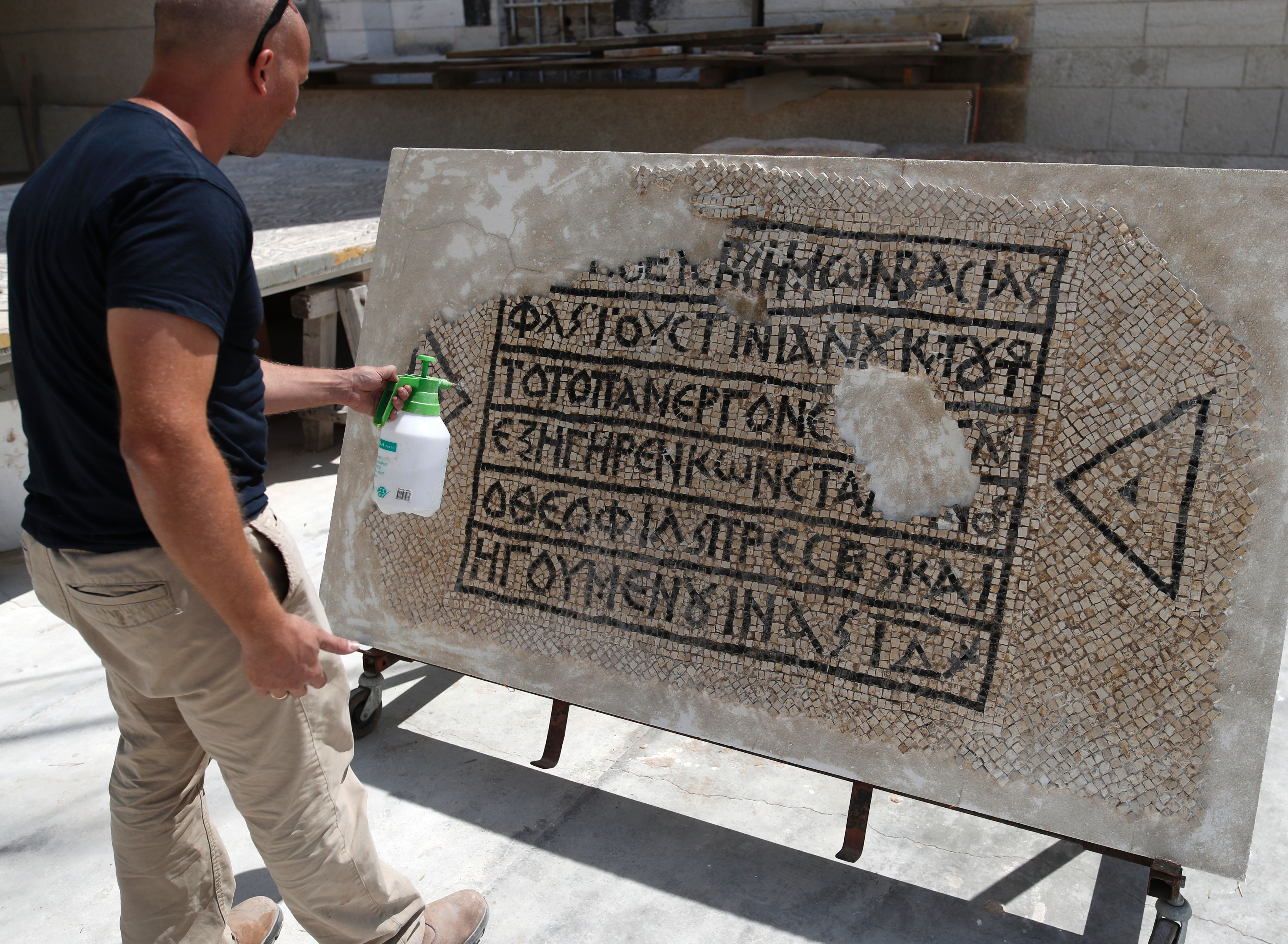 An archaeologist works on part of a 1,500-year-old mosaic floor bearing the names of Byzantine Emperor Justinian, at the Rockefeller Museum in Jerusalem, on August 23, 2017, after they unearth a portion of ancient mosaic near the city's Damascus Gate. (AHMAD GHARABLI/AFP/Getty Images)