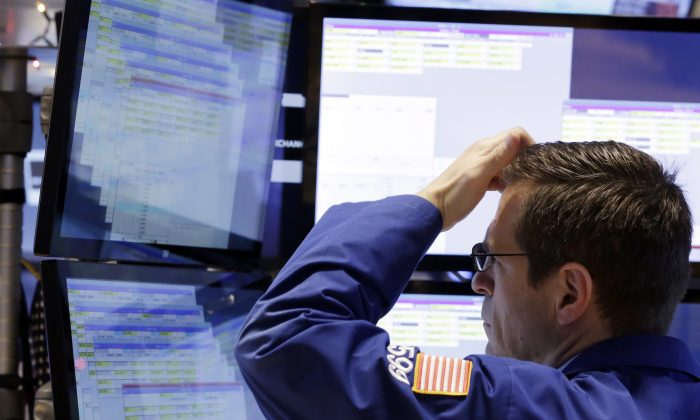 A trader works at his post on the floor of the New York Stock Exchange in this file photo. A reduction in risk-taking in the high-yield bond market signals that investors are starting to take a more defensive posture. (AP Photo/Richard Drew, File)