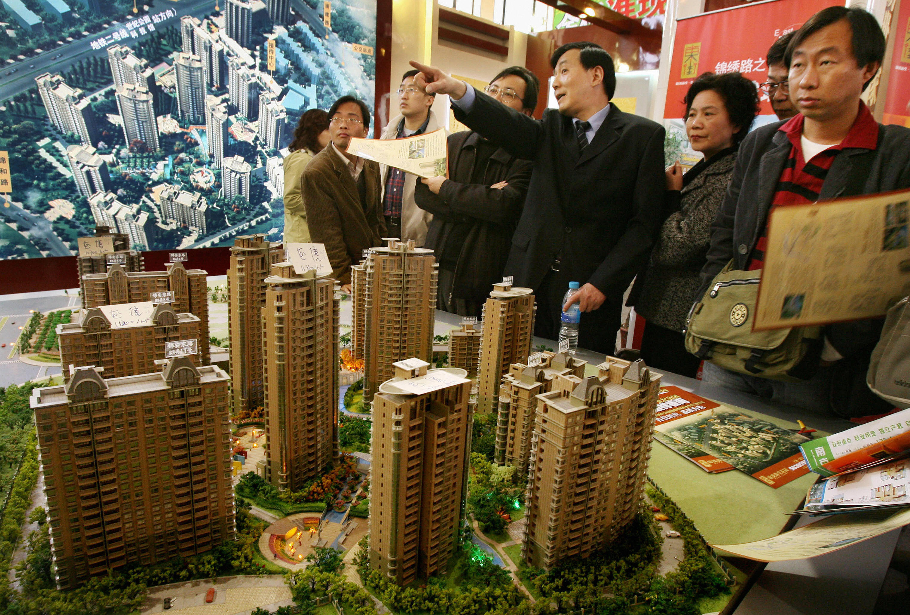 A property salesman (C) talks to potential buyers at a property exhibition in Shanghai on March 19, 2006. (MARK RALSTON/AFP/Getty Images)