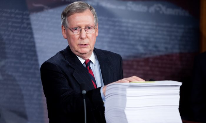 Then Senate Minority Leader Mitch McConnell (R-KY), with a copy of the Senate's health care reform legislation in front of him, holds a news conference regarding the bill on Capitol Hill on Nov. 21, 2009. (Brendan Hoffman/Getty Images)