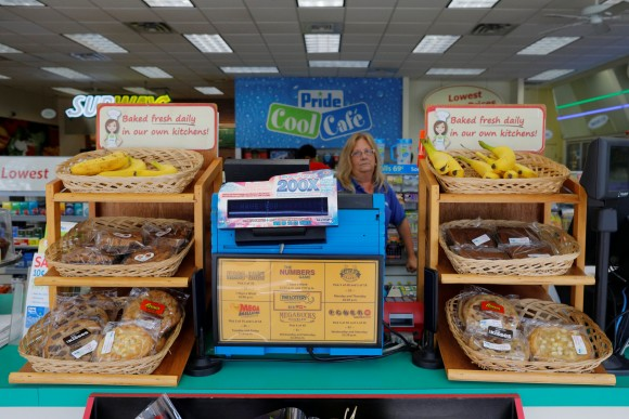 An employee stands behind a lottery machine at the Pride convenience store where a winning more than $750 million Powerball ticket was sold in Chicopee, Massachusetts, U.S., August 24, 2017.   (REUTERS/Brian Snyder)