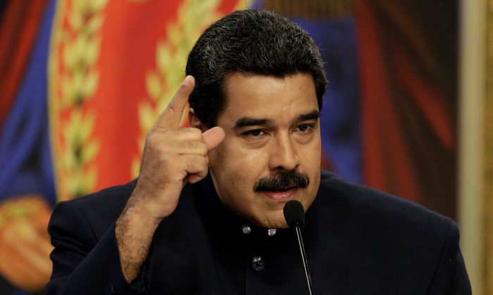 Venezuela's President Nicolas Maduro talks to the media in front of images of Venezuela's national hero Simon Bolivar, during a news conference at Miraflores Palace in Caracas, Venezuela on Aug. 22, 2017. (REUTERS/Marco Bello)
