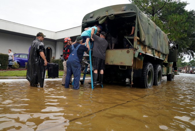 Volunteers load people into a collector's vintage military truck to evacuate them from flood waters from Hurricane Harvey in Dickinson, Texas, U.S. on Aug. 27, 2017. (REUTERS/Rick Wilking)