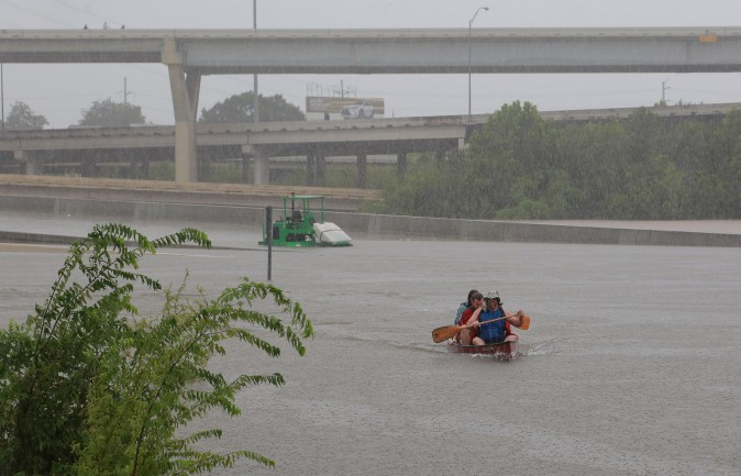 Area residents use a kayak to rescue motorists stranded on Interstate highway 45 in Houston. (REUTERS/Richard Carson)