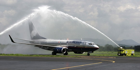 An Aeromexico plane crosses below an arc of water made by firefighters to mark the Mexico-Managua non stop inaugural flight 04 June 2007 in Managua.(MIGUEL ALVAREZ/AFP/Getty Images)