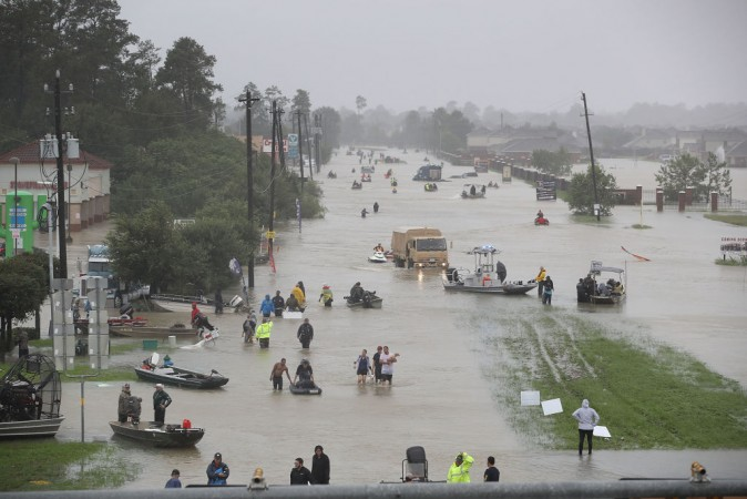 People walk down a flooded street as they evacuate their homes after the area was inundated with flooding from Hurricane Harvey on August 28, 2017 in Houston, Texas. Harvey, which made landfall north of Corpus Christi late Friday evening, is expected to dump upwards to 40 inches of rain in Texas over the next couple of days.  (Joe Raedle/Getty Images)