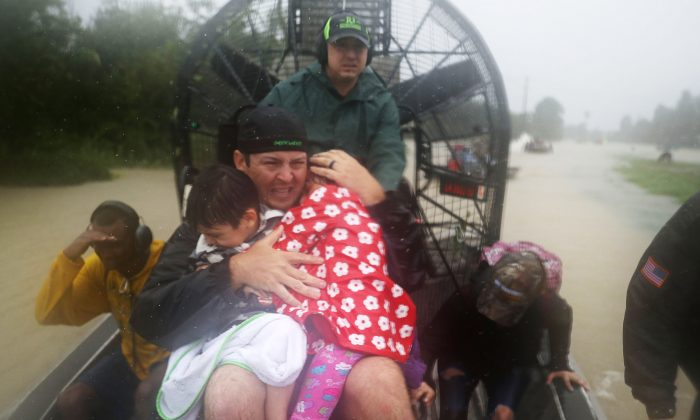 Volunteer Dean Mize  holds children as he and Jason Legnon use an airboat to rescue people from homes that are inundated with flooding from Hurricane Harvey in Houston, Texas on Aug. 28, 2017. (Joe Raedle/Getty Images)