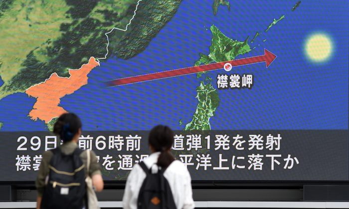 Pedestrians watch the news on screen displaying a map of Japan (R) and the Korean Peninsula, in Tokyo on Aug. 29, 2017. The North Korean regime fired a missile over Japan's northern Hokkaido island.(TOSHIFUMI KITAMURA/AFP/Getty Images)