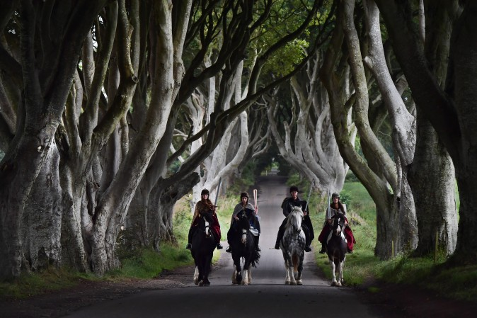 "Four actors dressed in costumes related to ""Game of Thrones"" carry the Queen's Baton as they make their way along the Dark Hedges in Ballymoney, Northern Ireland, on Aug. 29, 2017. The Queen's Baton Relay is currently on a tour of the United Kingdom as it makes its way around Europe in preparation for the 2018 Commonwealth Games in Australia. The Dark Hedges featured as the King's Road in season two of drama series ""Game of Thrones"" has become a tourist mecca for fans of the television series. (Charles McQuillan/Getty Images)"