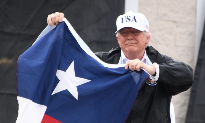 """President Donald Trump holds a Texas state flag outside of a fire house in Corpus Christi, Texas, on Aug. 29, where he received a briefing on the response to Hurricane Harvey. Trump thanked hundreds of people who had gathered outside of the fire station and said that """"Texas can handle anything."""" (JIM WATSON/AFP/Getty Images)"""