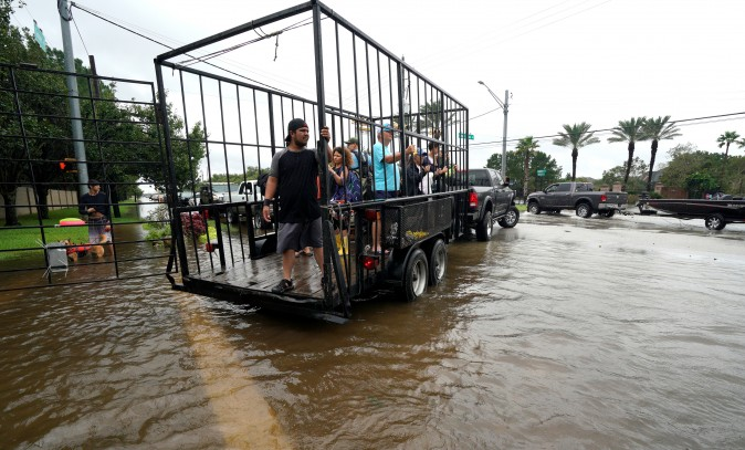A group of people are shuttled to dry ground in a trailer after being evacuated by boat from the Hurricane Harvey floodwaters in Houston, Texas August 29, 2017. (Reuters/Rick Wilking)