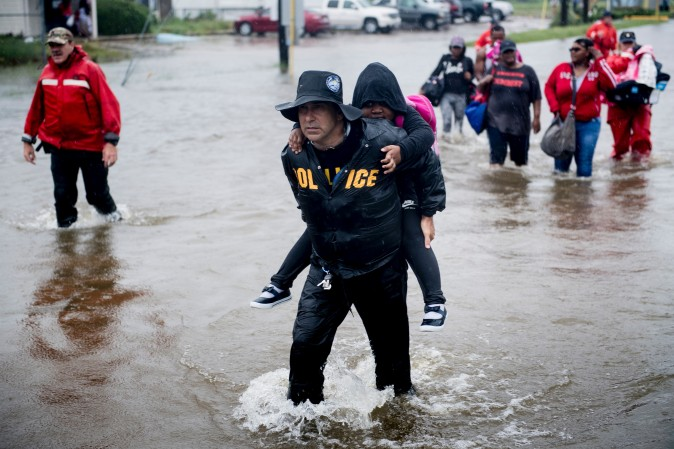 People walk to a Harris County Sheriff air boat while escaping a flooded neighbourhood during the aftermath of Hurricane Harvey on Aug. 29 in Houston, Texas. (BRENDAN SMIALOWSKI/AFP/Getty Images)