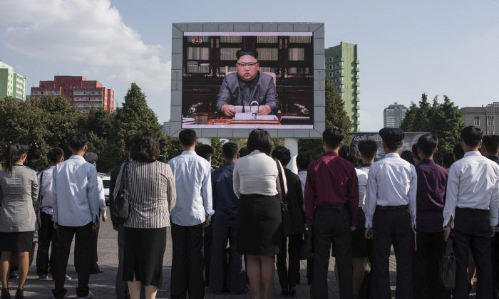 North Koreans watch a statement delivered by dictator Kim Jong Un on a television screen outside of the railway station in Pyongyang on Sept. 22. (Ed Jones/AFP/Getty Images)