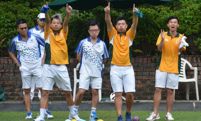 Wong Chun Yat (left in yellow) and Bronson Fung of Craigengower Cricket Club applaud a shot from their skipper during the league match against leaders Hong Kong Football Club last weekend, Sept 23, 2017. The rink won the game comfortably and helped CCC to an 8-0 victory. (Stephanie Worth)