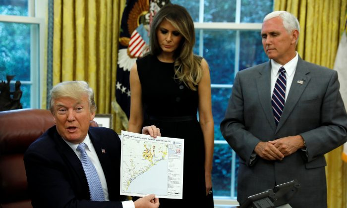 U.S. first lady Melania Trump and Vice President Mike Pence stand by U.S. President Donald Trump as he holds up FEMA map of damage assessment in Texas caused by Hurricane Harvey at the White House in Washington, U.S., September 1, 2017.  (REUTERS/Kevin Lamarque)