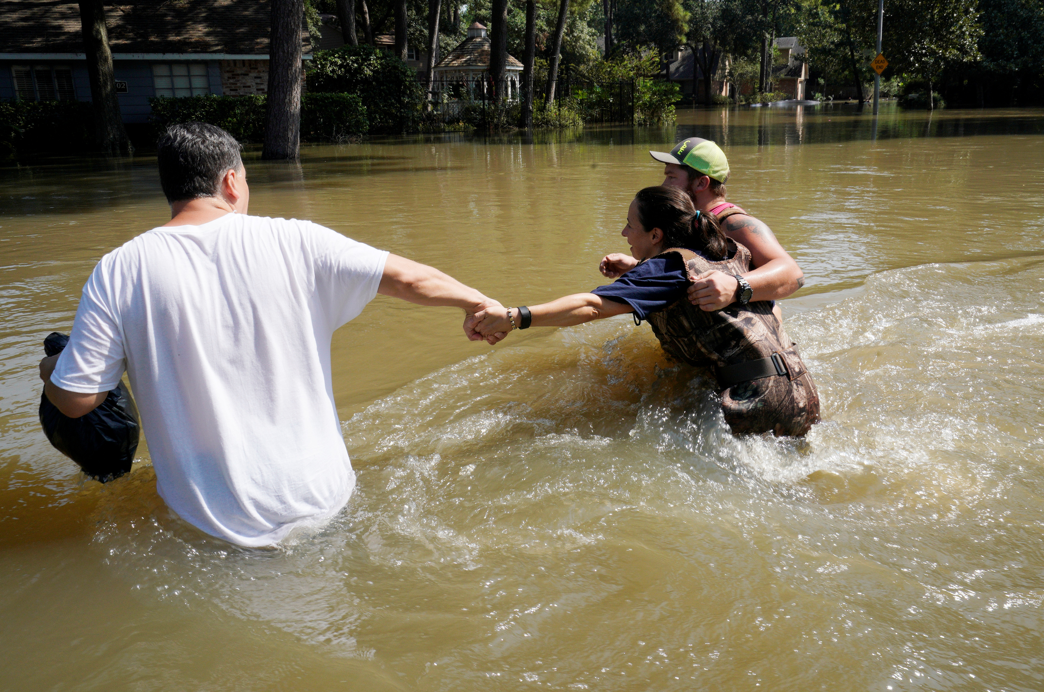 Melissa Ramirez (C) struggles against the current flowing down a flooded street helped by Edward Ramirez (L) and Cody Collinsworth as she tried to return to her home for the first time since Harvey floodwaters arrived in Houston, Texas on Sept. 1, 2017. (REUTERS/Rick Wilking)