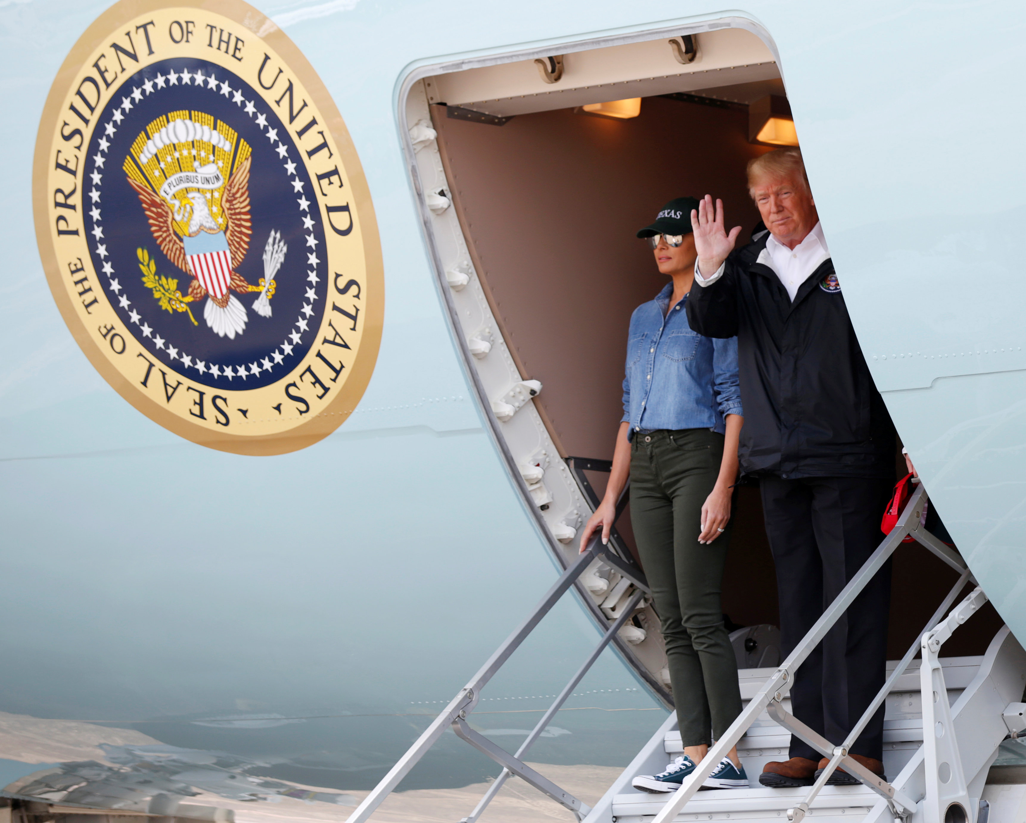 U.S. President Donald Trump and first lady Melania Trump wave from Air Force One after arriving at Ellington Field to meet with flood survivors and volunteers who assisted in relief efforts in the aftermath of Hurricane Harvey, in Houston, Texas, U.S., September 2, 2017.   REUTERS/Kevin Lamarque
