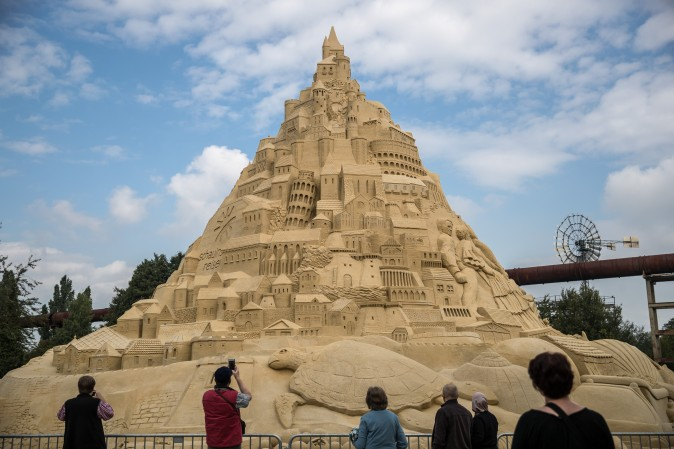 Visitors stand near the Sandburg sandcastle in Duisburg, Germany, on Sept. 1, 2017. A local travel agency commissioned the building of the sandcastle and sought to beat the previous world record of 14.84 meters and make it with 16.68 meters to set the new Guinness Book of World Record. The Sandburg took three weeks to build and is made from 3,500 tons of sand. (Maja Hitij/Getty Images)
