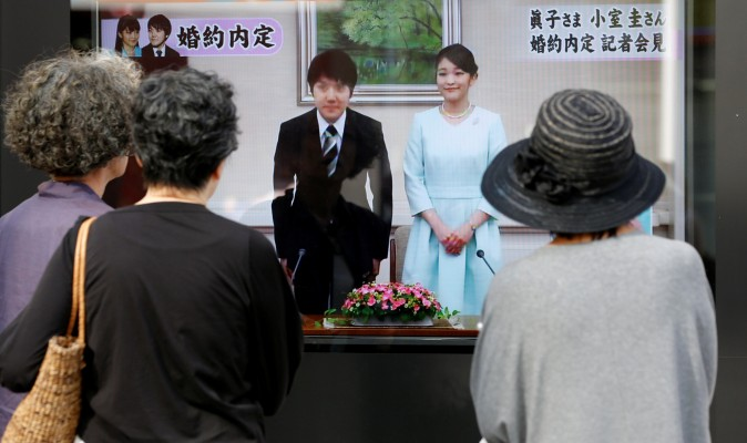 People look at a street monitor showing a news report about the engagement of Princess Mako, the elder daughter of Prince Akishino and Princess Kiko, and her fiancee Kei Komuro, a university friend, in Tokyo, Japan on September 3, 2017. (REUTERS/Toru Hanai)