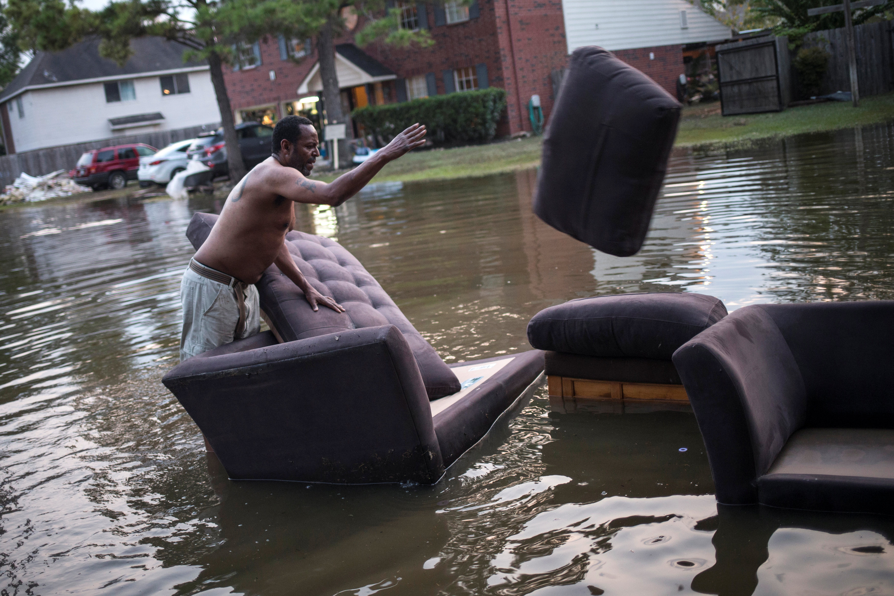 Vince Ware moves his sofas onto the sidewalk from his house which was left flooded from Tropical Storm Harvey in Houston, Texas on Sept. 3, 2017. (REUTERS/Adrees Latif)