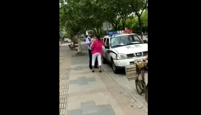 The moment before the police officer slams the woman and child to the pavement (YouTube/screenshot)