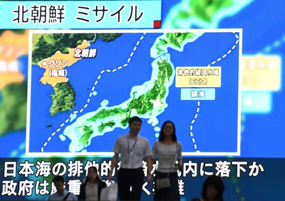 This picture taken on July 4, 2017 in Tokyo shows pedestrians walking past a large screen displaying a map of Japan (R) and the Korean Peninsula. (KAZUHIRO NOGI/AFP/Getty Images)