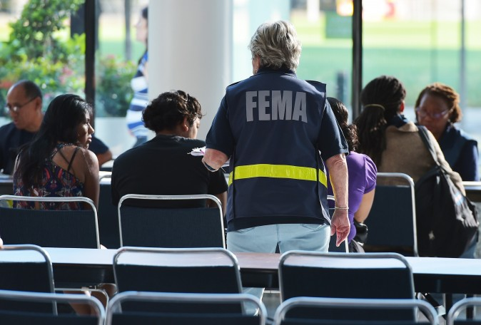 Federal Emergency Management Agency (FEMA) officials help people with questions at the George R. Brown Convention Center which has been a shelter for evacuees from Hurricane Harvey, in Houston on September 2, 2017. One week after Harvey blasted into southeast Texas as a Category Four hurricane, rescuers were still searching by air and by boat for people trapped in flooded homes. / AFP PHOTO / MANDEL NGAN        (Photo credit should read MANDEL NGAN/AFP/Getty Images)