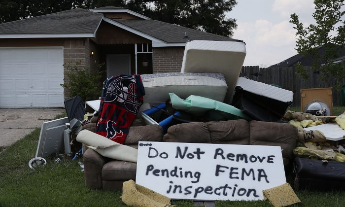 """A sign reading """"Do Not Remove Pending FEMA inspection"""" is seen with water logged items in front of a home after Hurricane and Tropical Storm Harvey on Sept. 2, 2017 in Houston, Texas. (Joe Raedle/Getty Images)"""