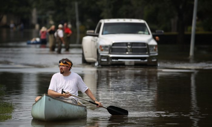 A man steers his canoe as he looks to help people retrieve items out of homes that were inundated with water during Hurricane and Tropical Storm Harvey.  (Photo by Joe Raedle/Getty Images)