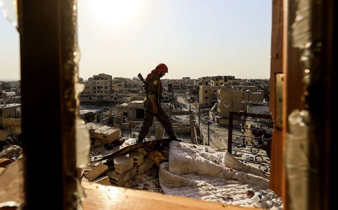 A member of the Syrian Democratic Forces (SDF), a US backed Kurdish-Arab alliance, walks on the roof of a building in the western al-Daraiya neighbourhood of the embattled northern Syrian city of Raqa on September 5, 2017, as they battle to retake the city from ISIS. (DELIL SOULEIMAN/AFP/Getty Images)