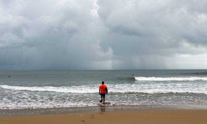 A surfer walks into the ocean in the waters of La Pared Beach in the aftermath of Hurricane Irma in Luquillo, Puerto Rico, on September 7, 2017. Puerto Rico was spare the brunt of Irma, though still suffered extensive damage. (RICARDO ARDUENGO/AFP/Getty Images)