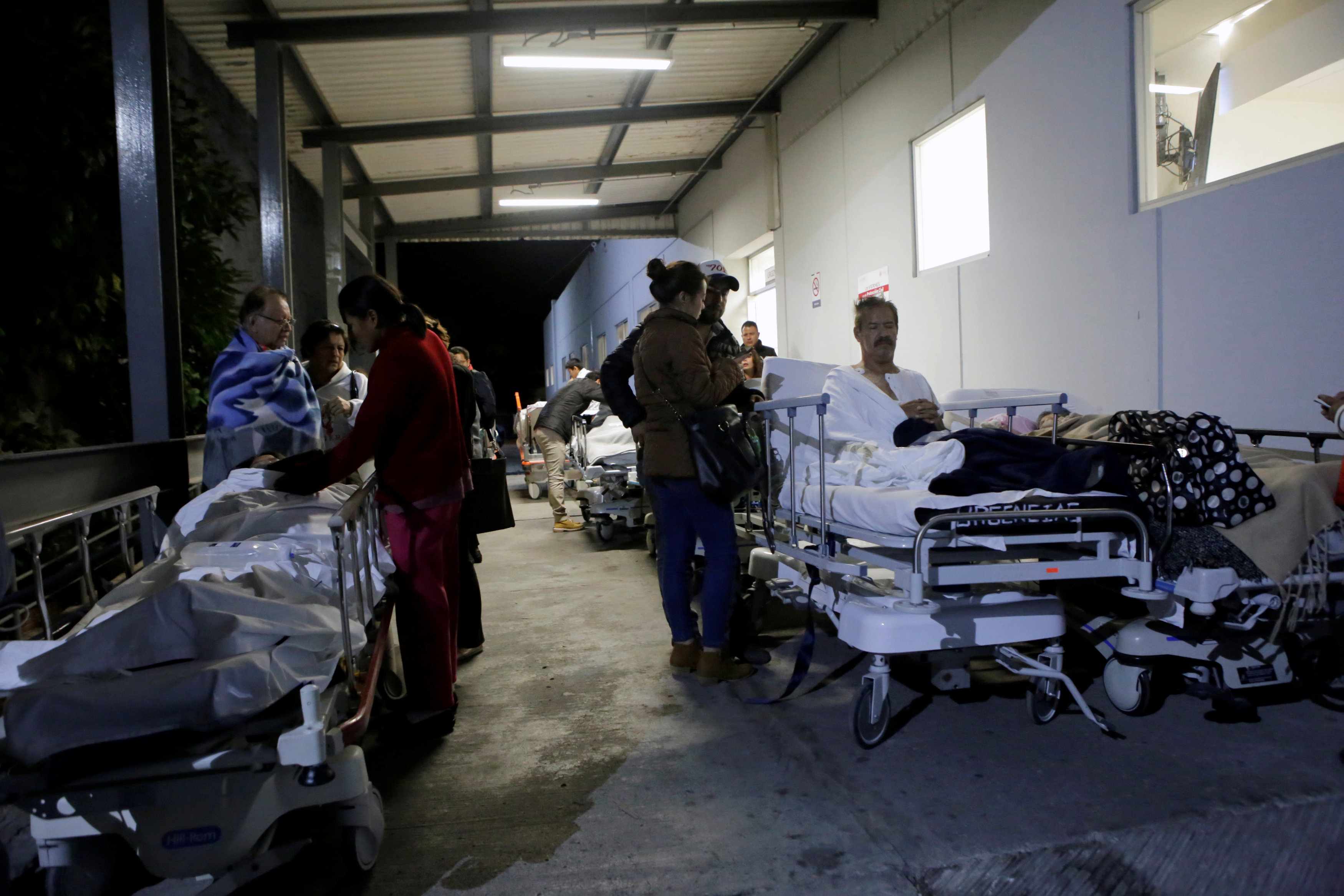 Patients and family members are seen outside the Institute for Social Security and Services for State Workers (ISSSTE) after an earthquake struck off the southern coast of Mexico late on Thursday, in Puebla, Mexico on Sept. 8, 2017. (REUTERS/Imelda Medina)