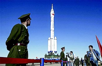 Military soldiers stand guard near the Shenzhou VI spacecraft at the Jiuquan Satellite Launch Center in Ejin, Inner Mongolia, on Oct. 7, 2005. (CHINA PHOTOS/GETTY IMAGES)